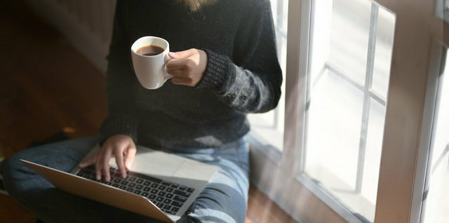 woman-using-laptop-while-holding-a-cup-of-coffee-3759083.jpg.jpe